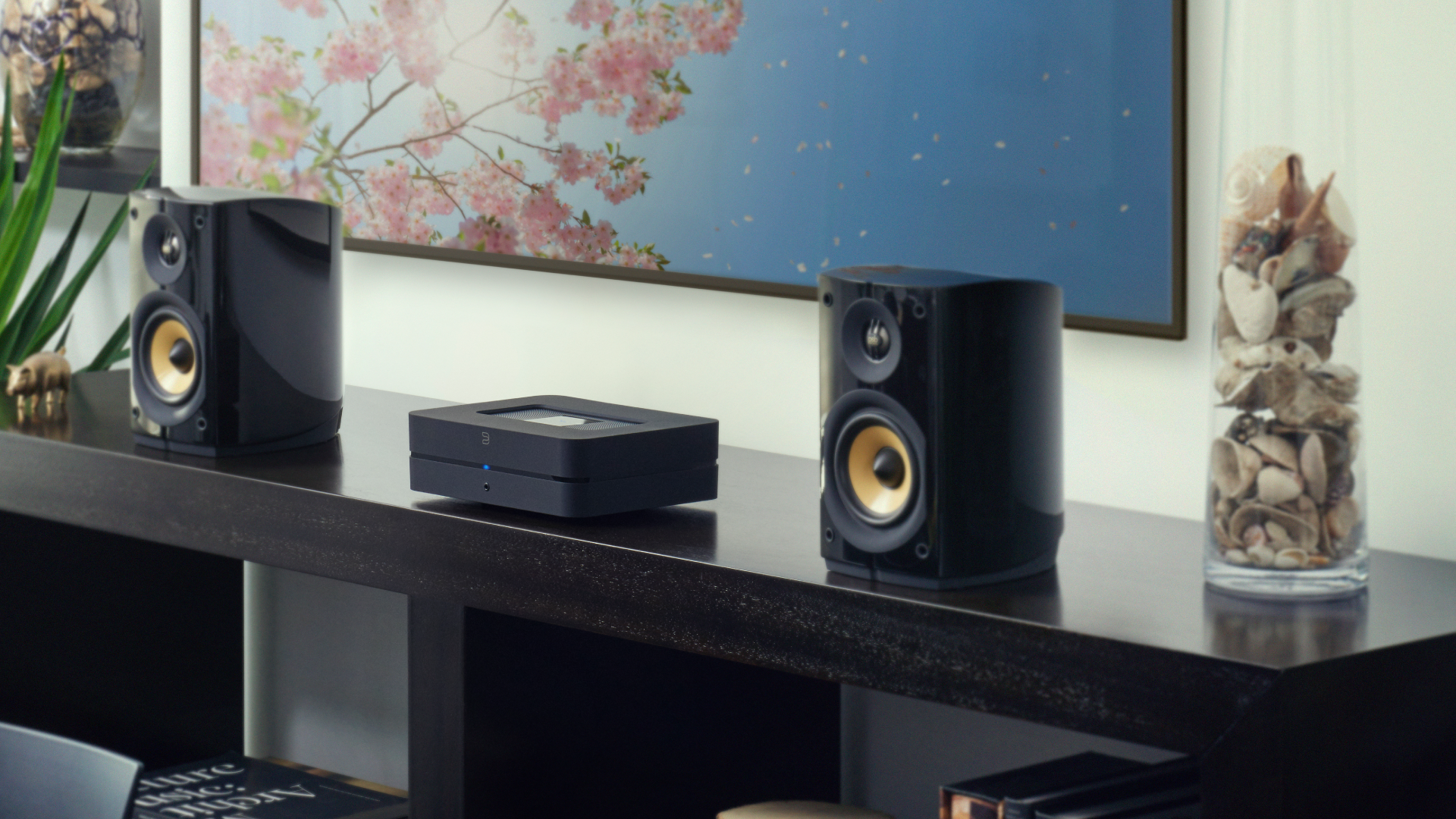 Bluesound POWERNODE on a shelf between a pair of speakers